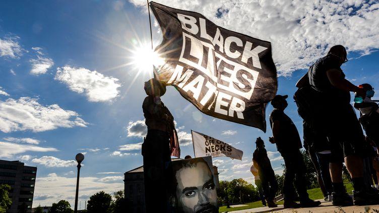 Une femme tient un drapeau Black Lives Matter lors d'une manifestation en souvenir de George Floyd, le 24 mai 2021 à Saint Paul, Minnesota. (KEREM YUCEL / AFP)
