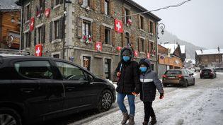 Une femme et un enfant marchent dans la station de ski de Châtel (Haute-Savoie) côté français, avec des drapeaux suisses derrière, le 1er décembre 2020. (FABRICE COFFRINI / AFP)
