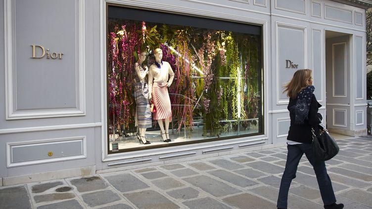 Une femme passe devant une boutique de luxe, avenue Montaigne, à Paris. (BLANCHOT PHILIPPE / HEMIS.FR / AFP)