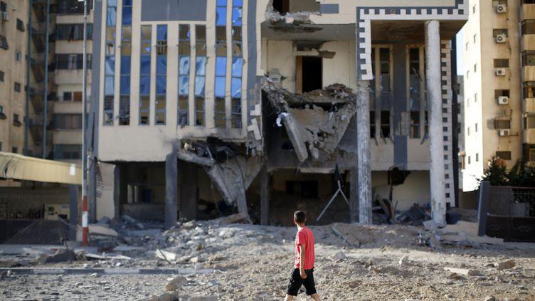 Un jeune Palestinien passe devant le bâtiment du Hamas dans la ville de Gaza, le 16 juillet 2014, après qu'une frappe israélienne l'a partiellement détruit. (THOMAS COEX / AFP)