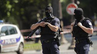 Des policiers en arme sur les Champs-Elysées à Paris, le 19 juin 2017, après la tentative d'attentat ratée. (THOMAS SAMSON / AFP)
