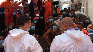 """Un médecin italien (à droite) fait face à des migrants secourus sur le navire humanitaire """"Ocean Viking"""", en Méditerranée, le 4 juillet 2020. (SHAHZAD ABDUL / AFP)"""