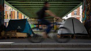 Un cyliste passe devant deux tentes de sans-abris sous la passerelle du bassin de la Villette à Paris le 3 juin 2020. (ANTOINE DE RAIGNIAC / HANS LUCAS / AFP)