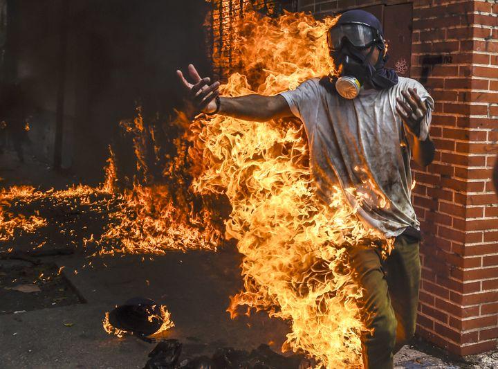 Transformé en boule de feu, Victor Salazar a été touché par l'explosion du réservoir d'une moto militaire qu'il avait incendiée, le 3 mai 2017 à Caracas (Venezuela). (JUAN BARRETO / AFP)