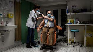 Une infirmière injecte une dose du vaccin Pfizer-BioNTech à un membre du personnel soignant de l'hôpital de la Croix-Rousse, à Lyon (Rhône), le 6 janvier 2021. (JEFF PACHOUD / AFP)