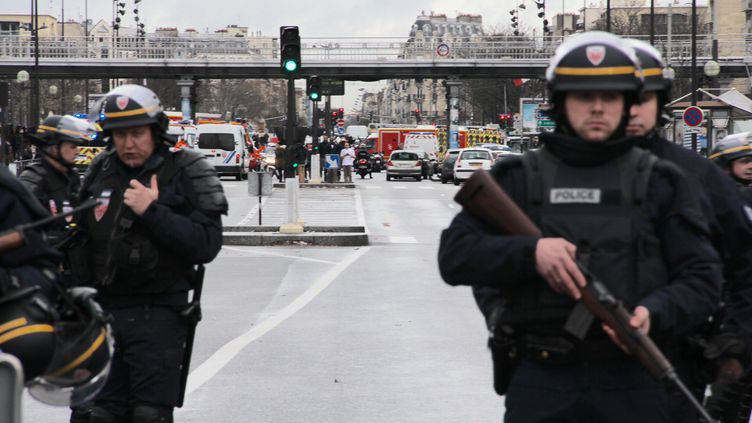Des policiers se tiennent prêts à intervenir aux abords d'une prise d'otages dans une épicerie casher, à Paris, le 9 janvier 2015. (BASTIEN HUGUES / FRANCETV INFO)