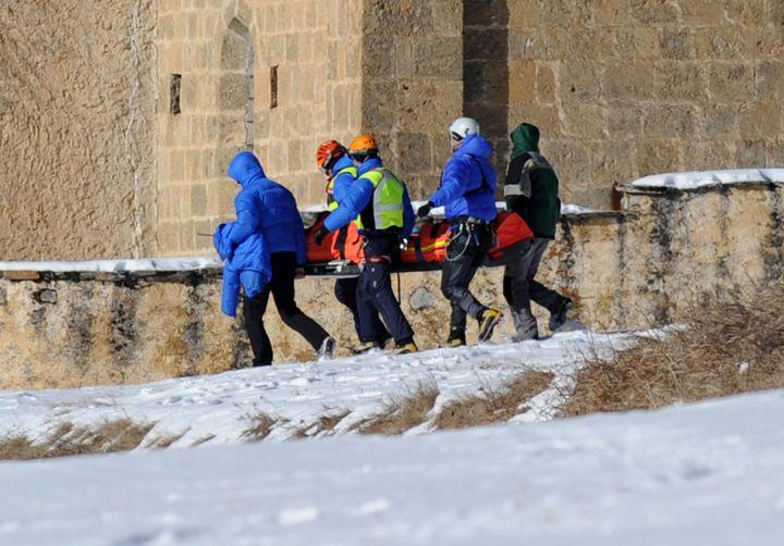 Des secouristes transportent le corps d'une victime d'avalanche à Ceillac (Hautes-Alpes), le 25 janvier 2015. (JEAN-PIERRE CLATOT / AFP)