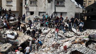 Des secours palestiniens recherchent des survivants sous les décombres d'un bâtiment détruit dans la ville de Gaza, le 16 mai 2021, à la suite du bombardement israélien. (MAJDI FATHI / NURPHOTO / AFP)