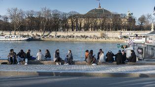 Des Parisiens sur les quais de Seine, le 28 février 2021 à Paris. (MAGALI COHEN / HANS LUCAS / AFP)