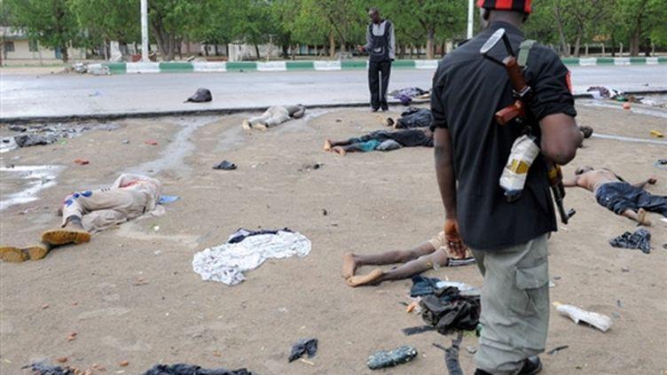 Un policier regarde les cadavres d'islamistes morts durant les combats le 28 juillet 2009 (© AFP Pius Utomi Ekpei)