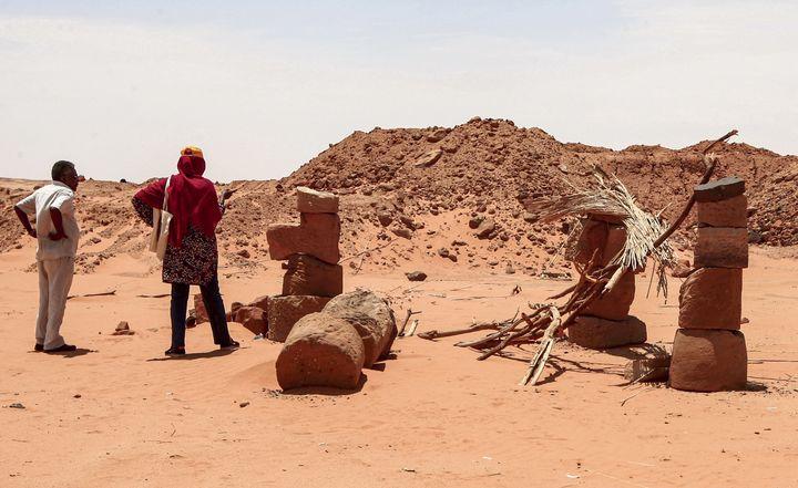 L'archéologue Habab Idriss Ahmed (à droite) et Mahmoud al-Tayeb, ancien expert du département des antiquités du Soudan, inspectent des pierres empilées les unes sur les autres et utilisées par des chercheurs d'or pour soutenir le toit d'une salle à manger sur le site millénaire de Jabal Maragha dans le désert du Bayoudas, à quelque 270 km au nord de la capitale Khartoum, le 20 août 2020. (EBRAHIM HAMID / AFP)