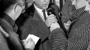 """L'écrivain Romain Gary, récompensé du prix Goncourt pour """"Les Racines du ciel"""", répond aux journalistes à l'aéroport d'Orly, le 13 décembre 1956. (STRINGER / AFP)"""