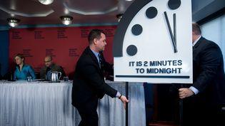 """Des membres du """"Bulletin of Atomic Scientists"""" présentent l'aiguille de l'horlogede l'apocalypse, qui symbolise l'imminence d'un cataclysme planétaire, à Washington (Etats-Unis), jeudi 25 janvier. (BRENDAN SMIALOWSKI / AFP)"""
