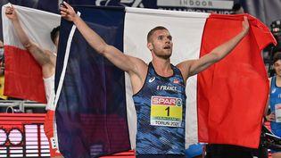 Kevin Mayer brandit le drapeau tricolore le 7 mars 2021 à Torun (Pologne) après son sacre en heptathlon aux championnats d'Europe d'athlétisme. (ANDREJ ISAKOVIC / AFP)