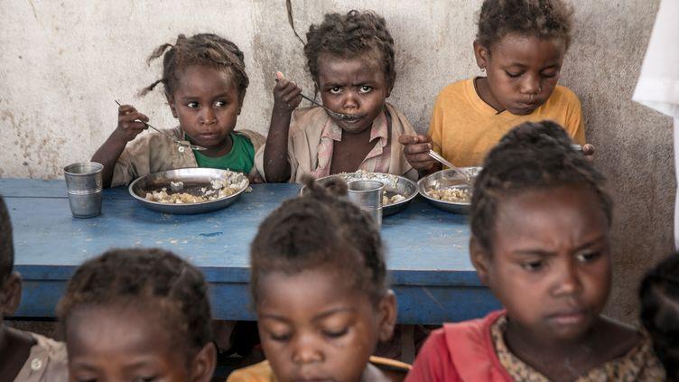 Des enfants mangent le repas fourni par le Programme alimentaire mondial dans une école au Sud de Madagascar, en décembre 2018.  (RIJASOLO / AFP)
