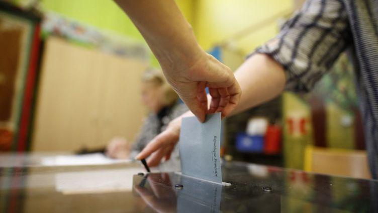 Dans un bureau de vote du 14e arrondissement de Paris, lors du second tour des élections législatives françaises, le 18 juin 2017. (BENJAMIN CREMEL / AFP)