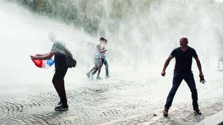 Des manifestants anti-pass sanitaire, le 24 juillet 2021 sur les Champs-Elysées à Paris. (CHRISTOPHE MICHEL / HANS LUCAS / A FP)