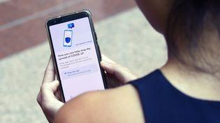 Une fonctionnaire du gouvernement de Singapour présente l'application de traçage de contacts TraceTogether, développée dans le cadre de la lutte contre le nouveau coronavirus, le 20 mars 2020. (CATHERINE LAI / AFP)