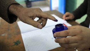 Un homme trempe son doigt dans de l'encre pour voter à Ben Arous (Tunisie), dimanche 21 décembre. (YASSINE GAIDI / ANADOLU AGENCY / AFP)