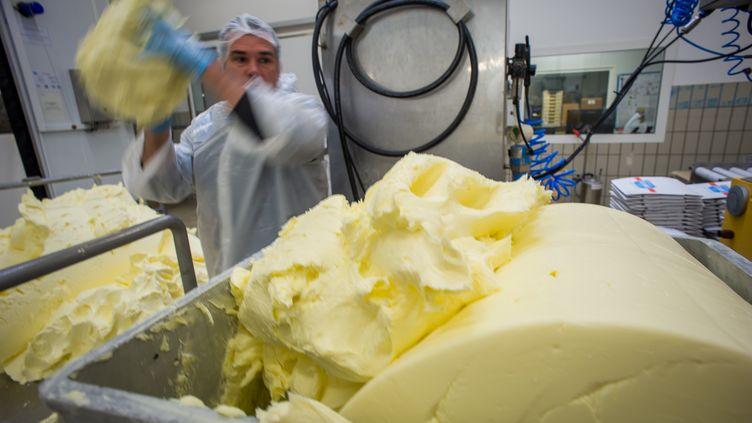 Un ouvrier manipule du beurre dans une laiterie à Echiré (Deux-Sèvres), le 17 mars 2015. (GUILLAUME SOUVANT / AFP)