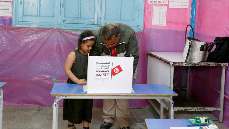 Un père et sa petite fille préparent le bulletin à mettre dans l'urne lors des élections municipales à Tunis le 29 avril 2018. (REUTERS - ZOUBEIR SOUISSI / X02856)