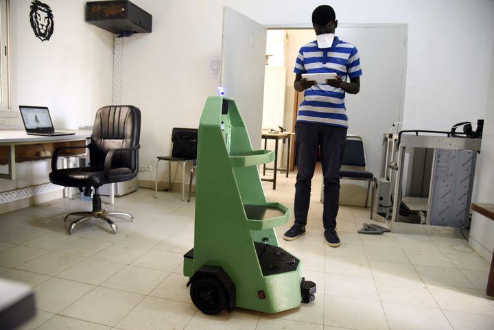 Pape Mamadou Gueye, étudiant en génie mécanique à l'Ecole Supérieure de Polytechnique (ESP) de Dakar, s'occupe d'un robot, le 8 mai 2020. (SEYLLOU / AFP)