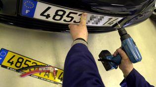 Un technicien installe une plaque d'immatriculation sur une voiture à Caen (Calvados), le 18 avril 2003. (MYCHELE DANIAU / AFP)
