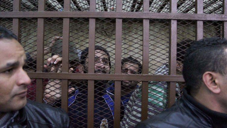 """Des prévenus laissent éclater leur soulagement après leur acquittement dans une affaire de """"débauche"""", le 12 janvier 2015, dans un tribunal du Caire (Egypte). (HASSAN MOHAMED / ANADOLU AGENCY / AFP)"""