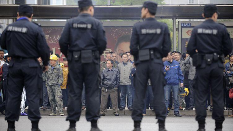 Des policiers montent la garde devant le tribunal où Liu Han, ancien président de Hanlong Group, est en procès à Xianning (province duHubei) en Chine, le 31 mars 2014. ( CHINA DAILY / AFP )