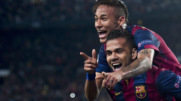Des joueurs du FC Barcelone, Neymar sur les épaules de Dani Alves, célèbrent un but face au PSG lors du quart de finale retour de la Ligue des Champions, à Barcelone (Espagne), le 21 avril 2015. (JOSEP LAGO / AFP)
