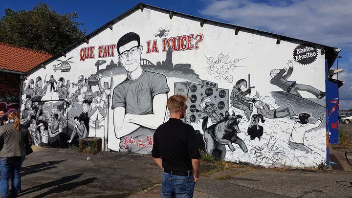 L'un des artistes qui ont réalisé la fresque à l'entrée du quai Wilson, à Nantes (Loire-Atlantique), le 18 juin 2020. (FABIEN MAGNENOU / FRANCEINFO)