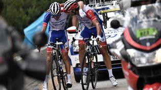 L'instant où Thibaut Pinot (à gauche) a mis pied à terre pour abandonner le Tour de France, blessé à la cuisse, vendredi 26 juillet 2019, lors de l'étape entre Saint-Jean-de-Maurienne et Tignes (Savoie). (MARCO BERTORELLO / AFP)