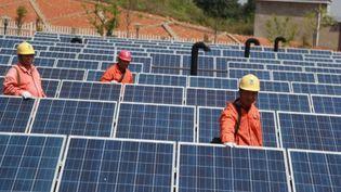 Des techniciens inspectent des panneaux solaires à Ningguo, dans la province d'Anhui (est de la Chine). (SONG WEIXING / IMAGINECHINA / AFP)