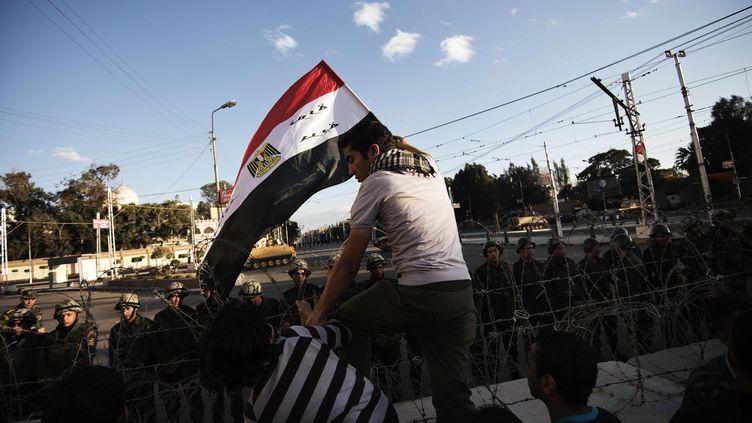 Un opposant à Mohamed Morsi franchit les barbelés aux abords du palais présidentiel, au Caire, le 7 décembre 2012. (GIANLUIGI GUERCIA / AFP)