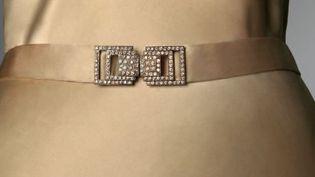 """Extrait de l'affiche de l'exposition """"Paris Haute Couture"""" / Madeleine Vionnet, robe du soir, vers 1931. Satin de soie ivoire, boucle en métal garni de cristaux.  (Collection Musée Galliera)"""