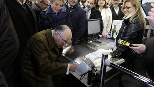 Le ministre de l'Intérieur, Bernard Cazeneuve, tente de payer ses achats avec sa carte bancaire, le 15 mars 2015 à l'Hyper Cacher de la Porte de Vincennes lors de la réouverture du supermarché. (KENZO TRIBOUILLARD / AFP)