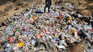 Un volontaire pose sur un monticule de déchets, cachés juste au delà de la ligne de mire destouristes sur un sentier du mont Everest, lors d'une opération de nettoyage en 2011. (CATERS NEWS AGENCY/SIPA)