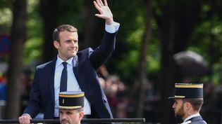 Emmanuel Macron salue la foule le 14 mai 2017 alor qu'il remonte les Champs-Elysées à Paris à l'occasion de sa prise de fonction. (CHRISTOPHE ARCHAMBAULT / AFP)