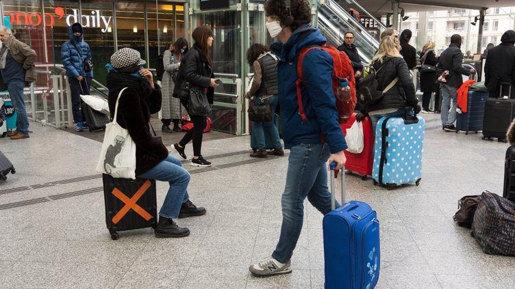 Des personnes s'apprêtent à prendre le train à la gare de Lyon à Paris, le 17 mars 2020, premier jour du confinement. (MASHA MOSCONI / HANS LUCAS / AFP)