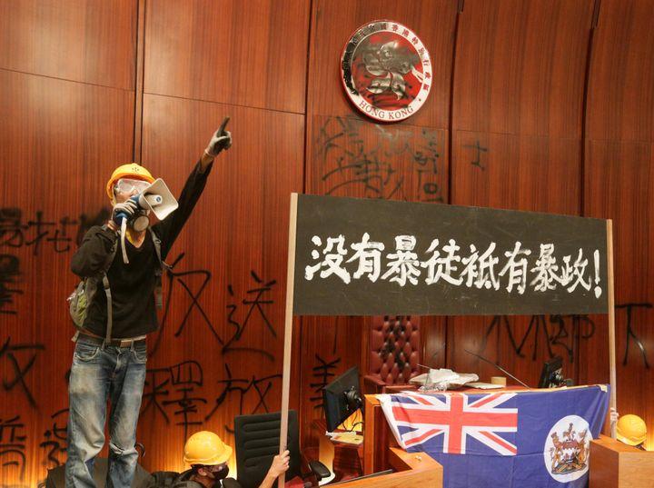 Un militant pro-démocratie à la tribune du Conseil législatif, à Hong-Kong, le 1er juillet 2019. (JUN YASUKAWA / THE YOMIURI SHIMBUN VIA AFP)