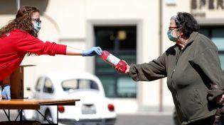 ACorreggio (Italie), une usine donne des bouteilles d'alcool que des membres de la Croix rouge distribuent, le 2 mai 2020. (EMMANUELE CIANCAGLINI / NURPHOTO / AFP)