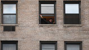 """Un hommeparticipe au rituel de 19 heures du confinement et chante""""New York, New York"""" à sa fenêtre, jeudi 16 avril 2020 à New York. (ANGELA WEISS / AFP)"""