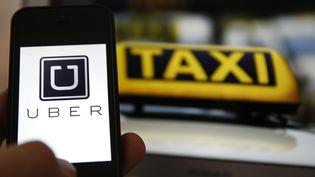 L'application pour smartphone Uber prise en photo devant un taxi, à Francfort (Allemagne), le 15 septembre 2014. (KAI PFAFFENBACH / REUTERS )