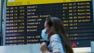 Une voyageuse à l'aéroport de Berlin (Allemagne), le 27 juillet 2020. (ANNETTE RIEDL / DPA / AFP)