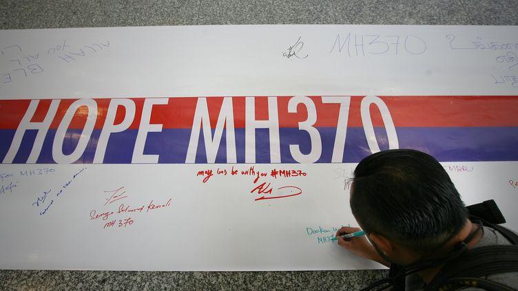 """Un Malaisien signe une banderole sur laquelle est écrit """"Espoir MH370"""", à Sépang, en Malaisie, dimanche 16 mars 2014. (EYEPRESSNEWS / AFP)"""