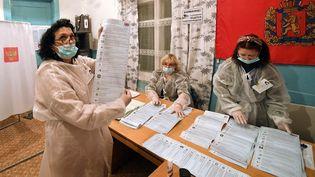 Des membres d'un comité local comptent les bulletins de vote lors des élections législatives russes, le 19 septembre 2021 àVerkhnyaya Biryusa (Russie). (ILYA NAYMUSHIN / SPUTNIK / AFP)