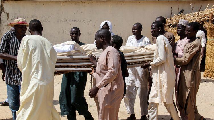Des hommes portent les corps de victimes d'une attaque de Boko Haram, le 26 juillet 2019, àDaloriprès deMaiduguri, au Nigeria. (AUDU MARTE / AFP)
