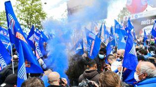Des policiers brandissant des drapeaux de leur syndicat Allance manifestent le 19 mai 2021 à Paris. (DOMINIQUE BOUTIN / SPUTNIK / AFP)