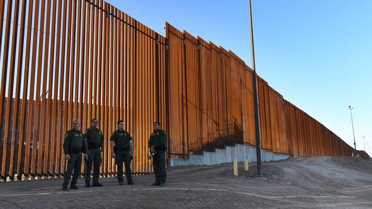 Desdouaniers américains devant une section du mur entre les Etats-Unis et le Mexique, le 26 octobre 2018. (MARK RALSTON / AFP)