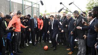 Emmanuel Macron tape sur un ballondevant des jeunes d'un quartier de Sarcelles (Val d'Oise), le 27 avril 2017 (MARTIN BUREAU / AFP)